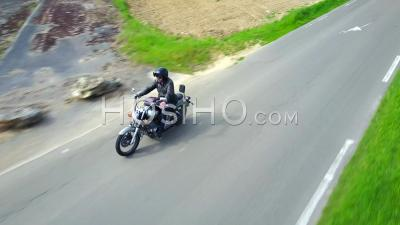 Biker On A Country Road, Followed By Drone
