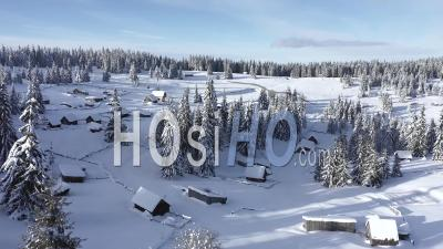 Epic Winter Scenery With Snow Covered Mountain Huts - Video Drone Footage