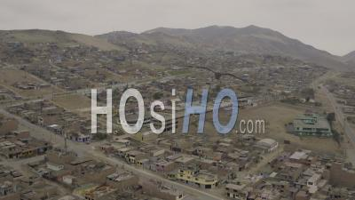 Ventanilla Peru Flying Low Backwards Over Urban Poverty Hillside Housing Area. - Video Drone Footage