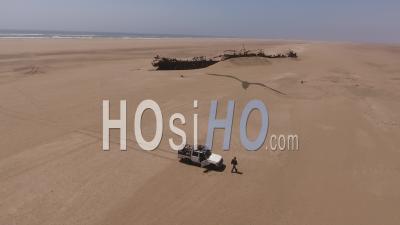Homme Sortant De La Voiture Pour Regarder L'épave Du Navire Eduard Bohlen, Désert Du Namib