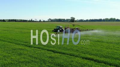 Tractor Spraying Chemical Products On Wheat Field - Video Drone Footage