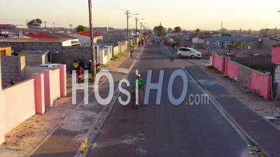 Aerial View Over Street Scene In Township Of South Africa, With Man And Shopping Cart Walking On Streets - Video Drone Footage