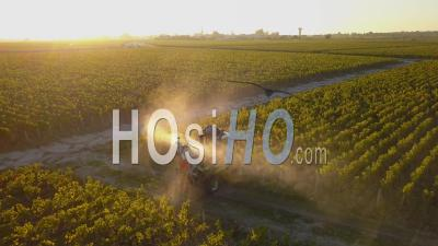 Tractor Spraying Rows Of Grape Vines In Bordeaux Vineyard At Sunrise