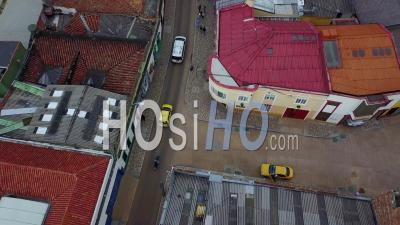 Aerial View Looking Down On A Taxi, Motorcycle And Car Driving On Streets In Bogota, Colombia - Video Drone Footage