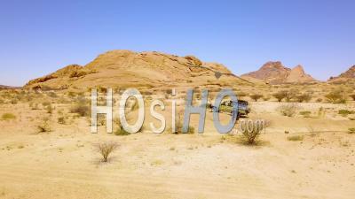 Vue Aérienne Sur Un Couple Marchant Près D'une Jeep Safari 4x4 Dans Le Paysage Désertique Accidenté De Spitzkoppe, Namibie, Afrique - Vidéo Drone