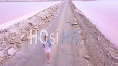 Aerial View Over A Woman Jogging Or Running On A Colorful Pink Salt Flat Region In Namibia, Africa - Video Drone Footage
