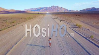 Aerial View Over A Woman Jogging Or Running On A Dirt Road In The Namib Desert In Namibia, Africa - Drone Point Of View