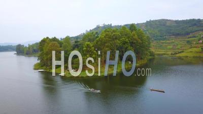 Aerial View Over A Motorboat Longboat Canoe Traveling On A Lake In A Lush Part Of Uganda, Africa - Drone Point Of View