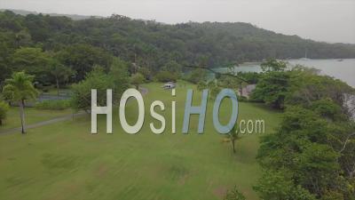 Vue Aérienne De L'hélicoptère D'un Complexe De Sandales Assis Sur Un Espace Ouvert Gazonné Sur Une île Tropicale Luxuriante En Jamaïque -Vidéo Drone
