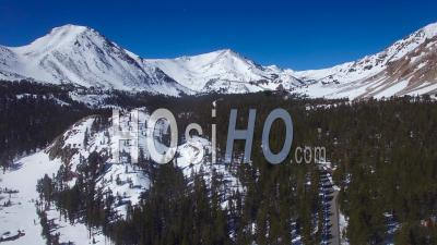Aerial View Over A Remote Road Through The Snowy Sierra Nevada Mountains In Winter - Video Drone Footage