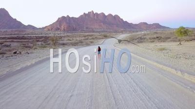 Aerial View Over A Woman Running On A Dirt Road Near Spitzkoppe, Namibia - Video Drone Footage