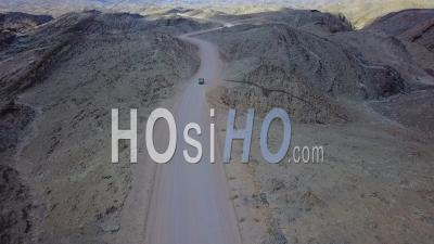 Aerial View Of A 4x4 Jeep Safari Vehicle On A Dirt Road Through The Mountains Of The Namib Desert In Namibia, Africa - Video Drone Footage