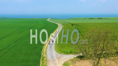 Aerial View Of A French Couple Riding Bicycles Through The Green Countryside Of Normandy, France - Drone Point Of View