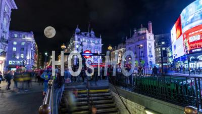 Piccadilly Circus In London At Night With Full Moon Raising