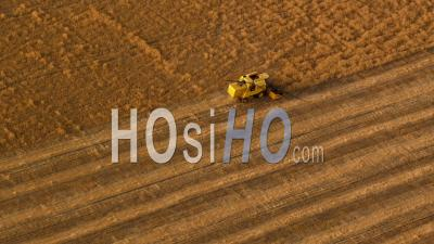 Aerial View Of Combine Harvester Working In Wheat Field