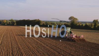 Tracteur Labourant Au Coucher Du Soleil Avec Une éolienne En Arrière Plan - Vidéo Drone