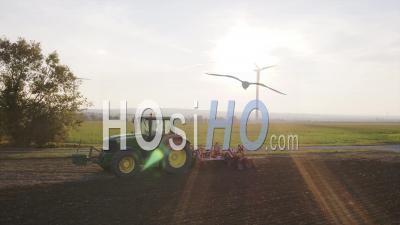 Gros Plan D'un Tracteur De Labour Au Coucher Du Soleil Avec Une éolienne En Arrière-Plan - Vidéo Drone