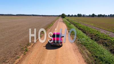 A Red Pickup Truck Traveling On A Dirt Road In A Rural Farm Area Of Mississippi - Aerial Video By Drone
