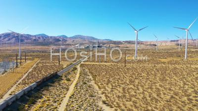 A Freight Train Traveling Through Vast Solar And Wind Array In Mojave Desert California - Aerial Video By Drone