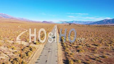 Aerial Of A 4wd Wheel Drive Vehicle On A Paved Road Across The Owens Valley Desert Region Suggests Remote Eastern Sierra Adventure. - Drone Point Of View