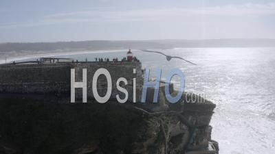 Close Shot Of Nazare's Lighthouse And Waves - Video Drone Footage