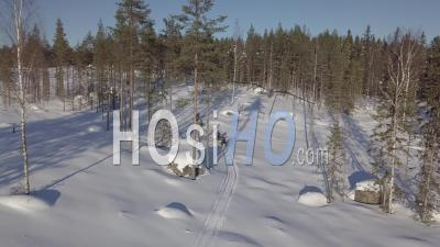 Two Snowmobiles Driving To A Snowy Forest Of Fir Trees, Tackasen, Sweden - Video Drone Footage