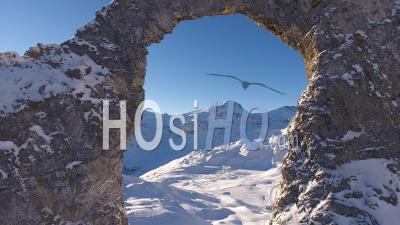 Natural Rock Bridge In The Snowy Alps Mountains, Tignes, France - Video Drone Footage