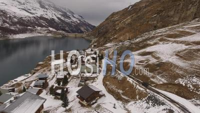 Car Driving On A Road Next To A Village Near A Lake In The Alps, Tignes, France - Video Drone Footage