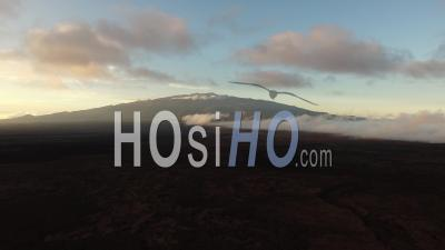 Large View Of The Sunset Behind Mauna Loa Volcano Coming Out The Clouds, Hawaii - Video Drone Footage