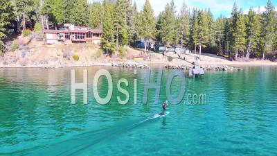 2020 - A Man Rides A Hydrofoil Efoil Electronic Surfboard Across Lake Tahoe, California In An Extreme Hydrofoiling Foil Sport Demonstration. - Video Drone Footage