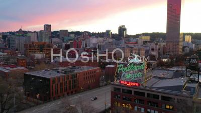 Aerial Past Portland Oregon Stag Deer Sign And Downtown Old Town Cityscape And Business District At Sunset Or Dusk. - Video Drone Footage