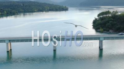 Aerial View Of Car Crossing The Bridge Over The Lake Of Saint Cassien, Drone Point Of View