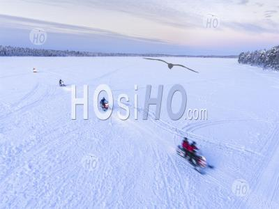 Aerial Drone Photo Of Snow Mobiles On A Snowmobiling Adventure On A Snow Covered Lake In Winter At Finnish Lapland, Finland