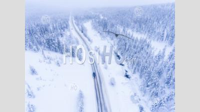 Aerial Of Car Driving On A Dangerous Winter Road In Bad Icy Conditions Next To Frozen River And Snow Covered Forest - Aerial Photography