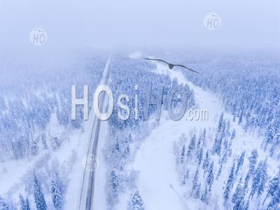 Aerial Of Winter Road By Frozen River And Snow Covered Forest Landscape Showing Lapland Scenery In Scandinavia In Finland - Aerial Photography