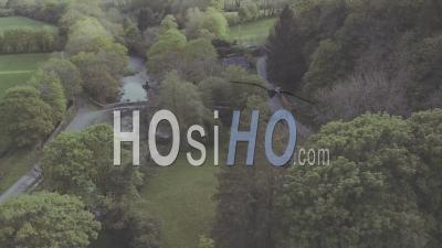 Black Car On A Curved Country Road Between Trees And Green Fields, On A Cloudy Day - Aerial Drone View