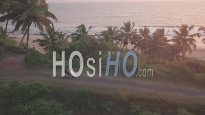 Motorcycle Rider Driving On The Road With Palm Trees In Varkala, India At Sunset Scenery By The Sea - Aerial Drone Shot