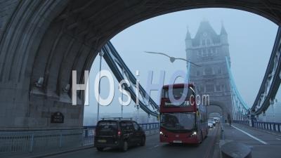 Red London Bus Driving In Traffic On Tower Bridge In London In Foggy Misty Weather On A Cool Blue Morning With Mist And Fog On First Day Of Coronavirus Covid-19 Lockdown, England, Europe
