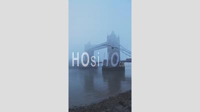 Vidéo Verticale De Tower Bridge Et De La Tamise Dans Le Brouillard Et Les Conditions Météorologiques Brumeuses Dans Le Centre-Ville De Londres Le Matin Atmosphérique Bleu Avec Brouillard Et Brouillard Dans Le Coronavirus Covid-19 Lockdown, England, Uk