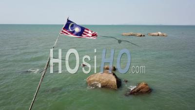 Malaysia Flag Waving At Background Rock - Video Drone Footage