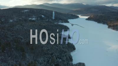 Waterbury Vermont Frozen Lake, New England Forest And Mountains In Winter At Sunset - Video Drone Footage
