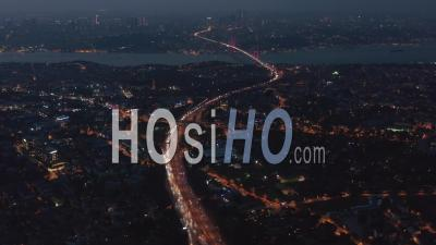 Highway Freeway Road Going Through Istanbul City With Red Illuminated Bosphorus Bridge In The Distance At Night, Aerial Wide View - Video Drone Footage