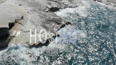 Aerial View Of Sarakiniko Lunar Volcanic Beach With Waves Crashing Into Rocks In Milos, Greece 4k - Video Drone Footage