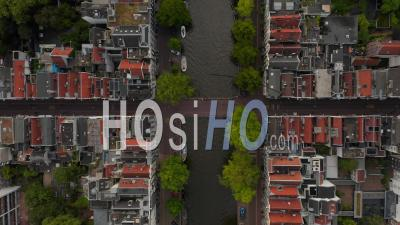 Amsterdam, Netherlands Canal Overhead Birds View With Boat Traffic And Red House Rooftops 4k - Video Drone Footage