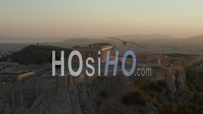 Aerial Flight Towards Acropolis Of Athens With Greek Flag Waving In Beautiful Golden Hour Sunset Light With Ocean In The Distance 4k - Video Drone Footage