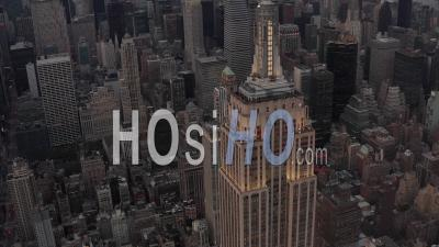 Aerial View Flying Away From The Empire State Building In The Evening Lights With Skyscrapers And Office Buildings In The Background 4k - Video Drone Footage