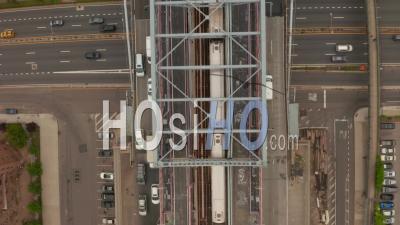 Vue Aérienne Aérienne De Haut En Bas à La Suite D'un Train De Métro Roulant Sur Le Pont De Williamsburg Et Traversant Une Autoroute à Voies Multiples Très Fréquentée à New York City 4k - Drone Vidéo