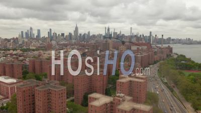 Slow Dolly Aerial Shot Of Alphabet City Residential Neighborhood And Multi Lane Car Traffic With New York City Skyscrapers In The Background On A Cloudy Day 4k - Video Drone Footage