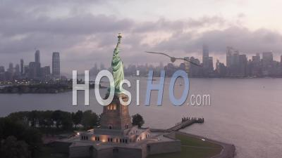 Statue De La Liberté Encerclée éclairée à La Lumière Du Matin Avec Les Toits De La Ville De New York Brumeux En Arrière-Plan 4k - Vidéo Aérienne Par Drone