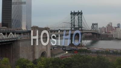 Vue Aérienne De Dolly Sur Le Front De Mer De La Rivière East, Volant Vers Le Pont De Manhattan Avec Un Trafic Intense Vers Brooklyn Et Un Hélicoptère Volant à Travers Le Ciel 4k - Drone Vidéo